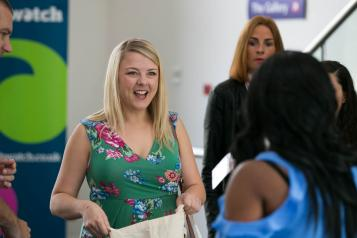 Woman smiling at a Healthwatch event, picking up promotional materials