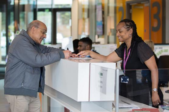 A Healthwatch volunteer speaks with a service user in a hospital reception area