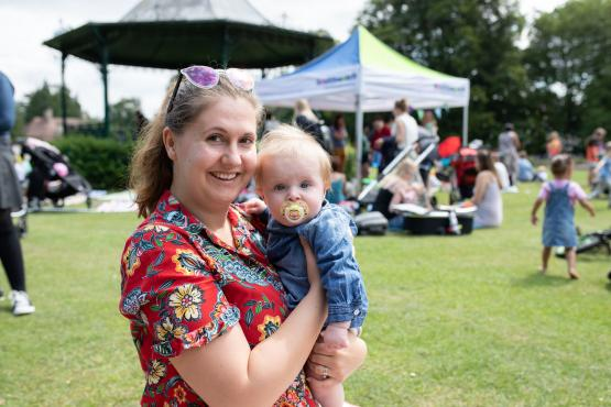 Woman holding a baby at healthwatch outdoor event