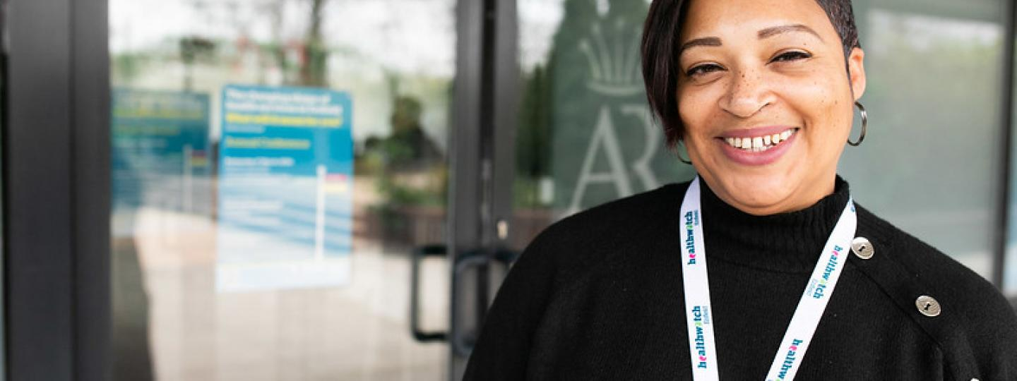 Woman smiling with a healthwatch lanyard on